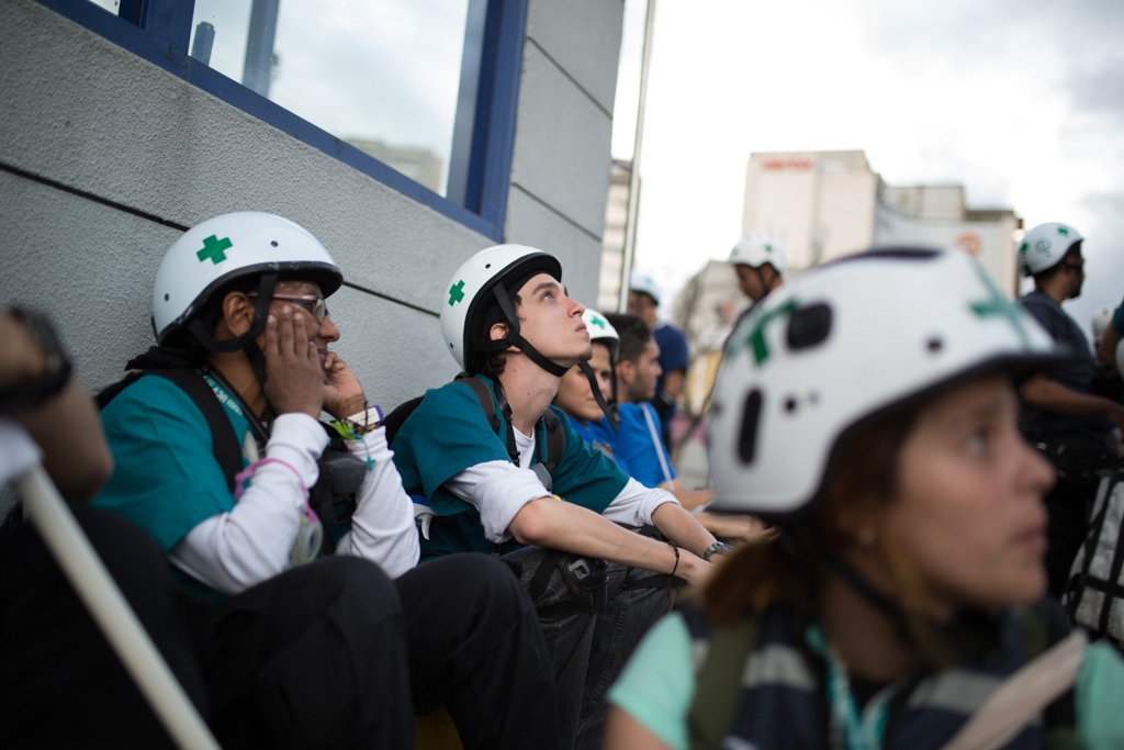 Once the protest is over, volunteers members of green cross take a break to rest and prepare themselves to come back to their meeting point.Tiredness and satisfaction are common feelings at the end of day. Libertador Avenue, Caracas, Venezuela. June 24, 2017.