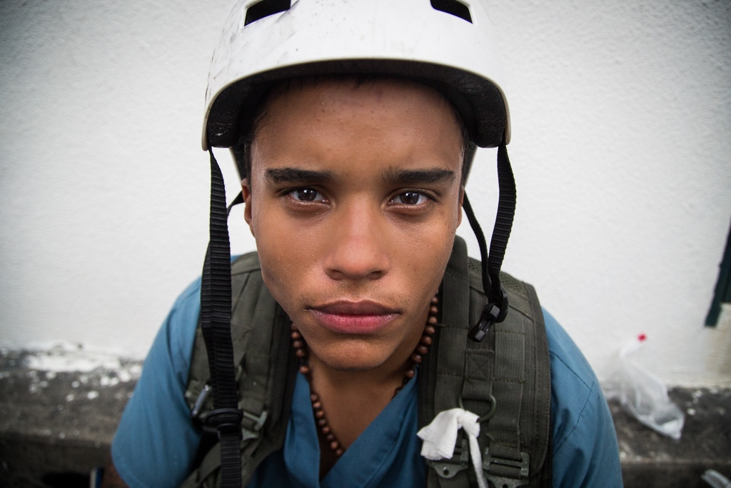 Volunteer member of green cross wearing helmet and bullet proof vest waits the moment to join the protest against venezuelan government. Torre Letonia, Caracas. Venezuela. May 10, 2017 Its members are mostly very young men and women in their 20s. Almost all of them study third of fourth year of Medicine at The Universidad Central de Venezuela. Nevertheless a group of practicing doctors with years of experience join the group in each protest.