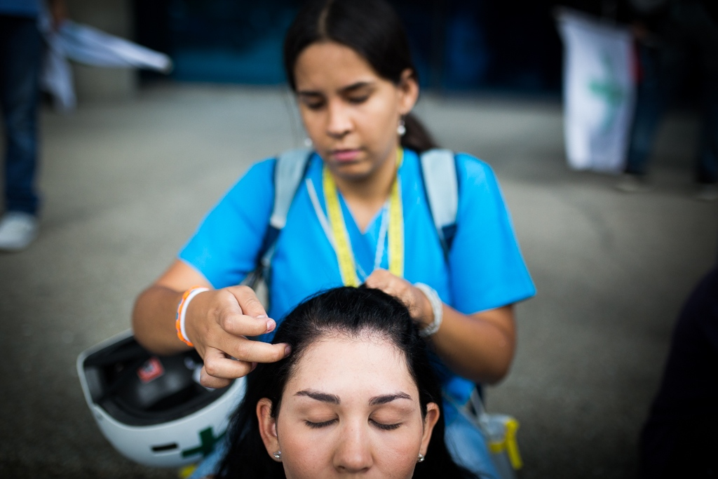 A girl medicine student member of Green Cross ties the hair of a companion as a security measure at the moment of wearing the antigas mask. Lido Mall, Caracas. Venezuela. May 24, 2017.