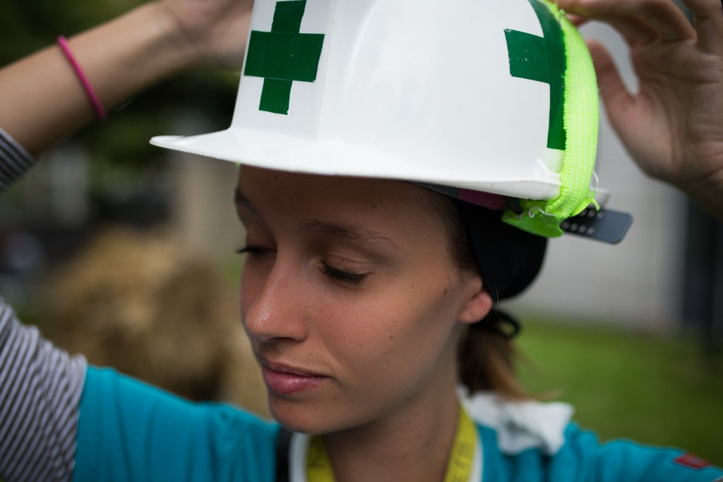 A medicine student part of Green Cross adjusts her white helmet before joining the protest.They are know as green cross because they wear all the time a white helmet with a green cross. Torre Letonia, Caracas. Venezuela. June 7, 2017.