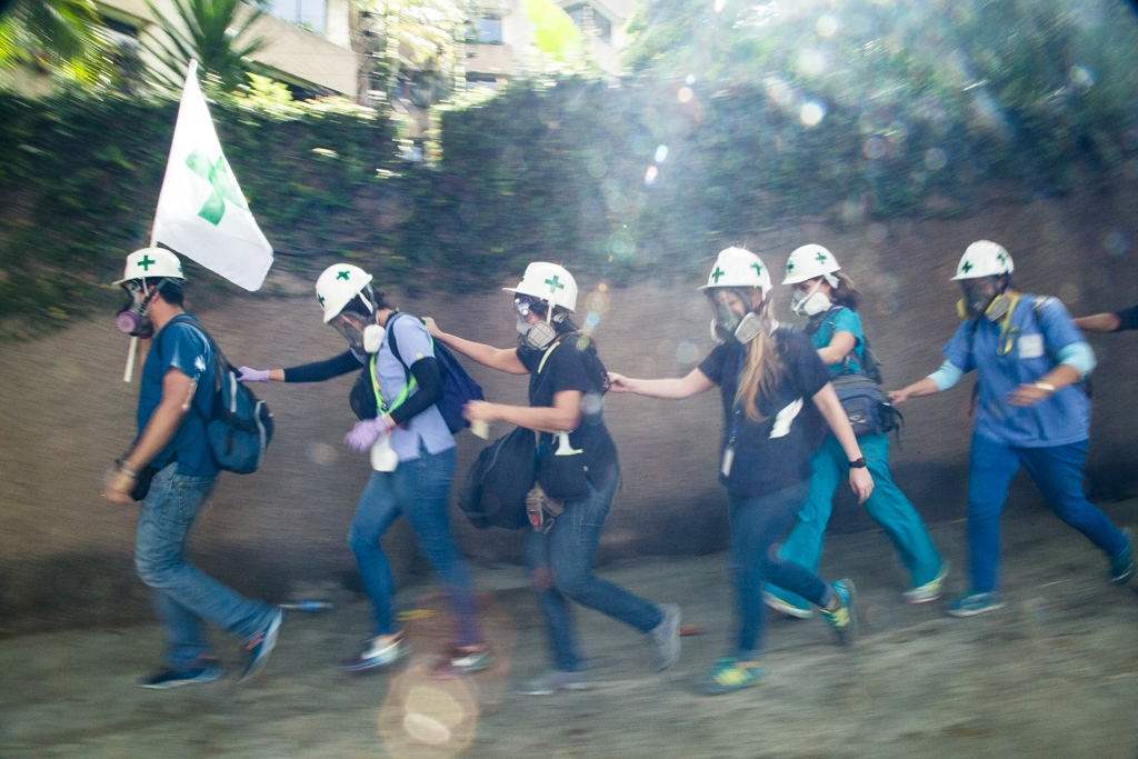 Volunteers members of green cross walk together in a line, as a security mesure, during a rally against Venezuelan government. La Castellana, Caracas. Venezuela. May 1, 2017.
