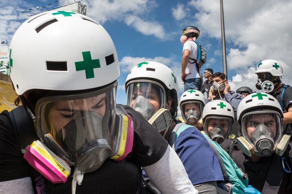 A group of green cross members takes position and carefully observes what happens during a rally against Venezuelan government. Francisco Fajardo highway. May 29, 2017. As part of their strategies they divide the conflict space into three zones, in each zone a group of ten volunteers is present. The green zone is 300 meters or more away from the clashes between protesters and the public force, there is where protesters are taken out to be seen by specialists or evacuated. The orange zone, 200 meters from the clashes, is where protesters are treated or immediately rushed out of the crowd. Finally the red zone, practically next to the conflict area, is where many of the wounded are either treated or sent to other zones.