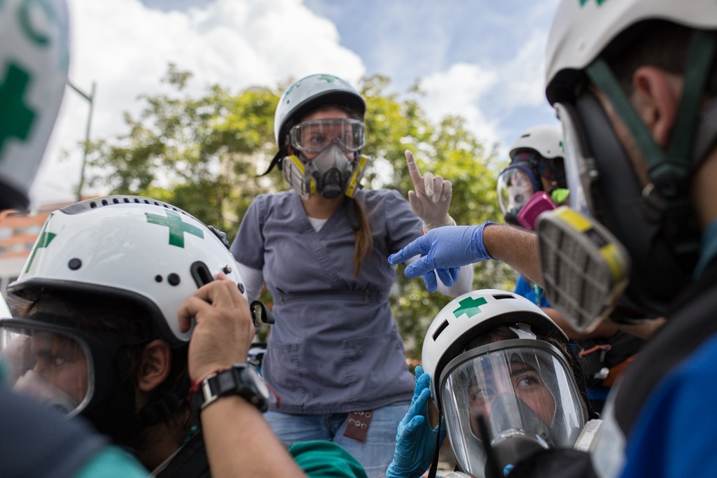 A group of green cross members discusses actions to be taken during a rally against venezuelan government. Constant communication between the members and the respect for the safety protocol has a vital importance in order to prevail the security of the group.Las Mercedes, Caracas. Venezuela. June 19, 2017.