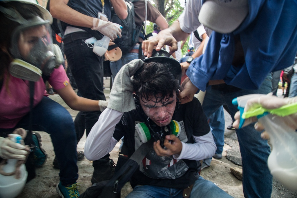 Green Cross volunteers spray water with malox to the face of an asphyxiated person consequence of the tear gas used by military forces to repress the protest. La Castellana, Caracas, Venezuela. May 1, 2017.