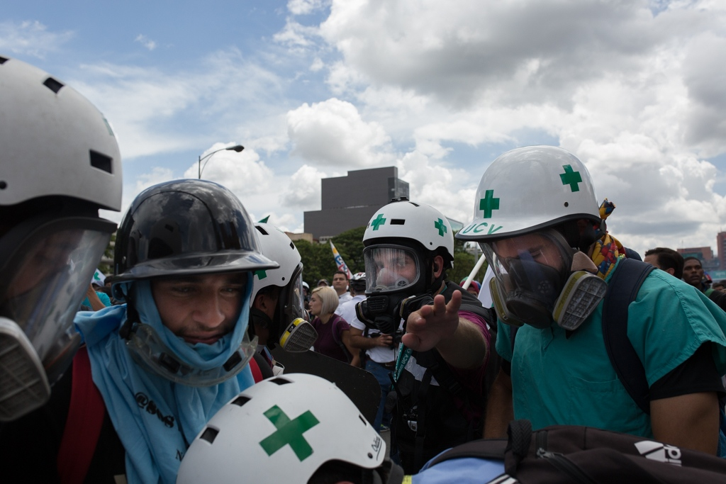Volunteers members of green cross give medical assistance to a injured person during a rally against venezuelan government. Francisco Fajardo Highway, Caracas, Venezuela. June 19, 2017.