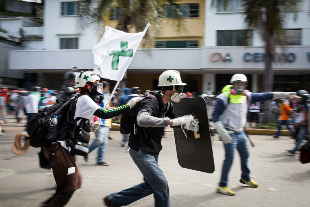 Volunteers members of green cross run to reach and give medical assistance to an injured person during an anti government rally. Las Mercedes, Caracas, Venezuela. May 29, 2017.