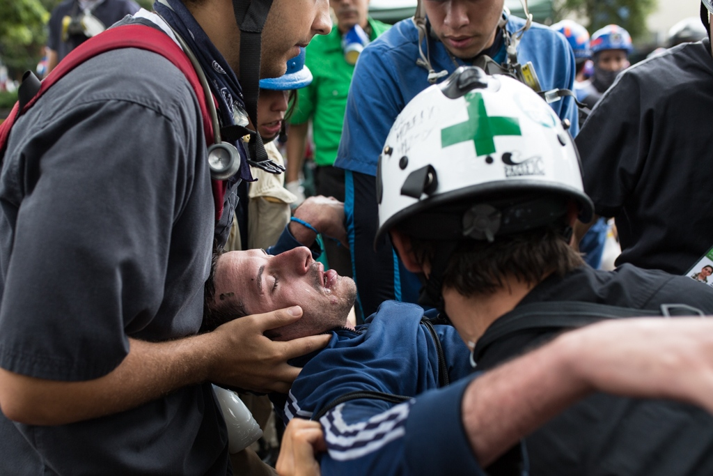 Volunteers members of green cross evacuate a severe injured person from the protest area to take him to a near health care center. Las Mercedes, Caracas. Venezuela. June 19, 2017.