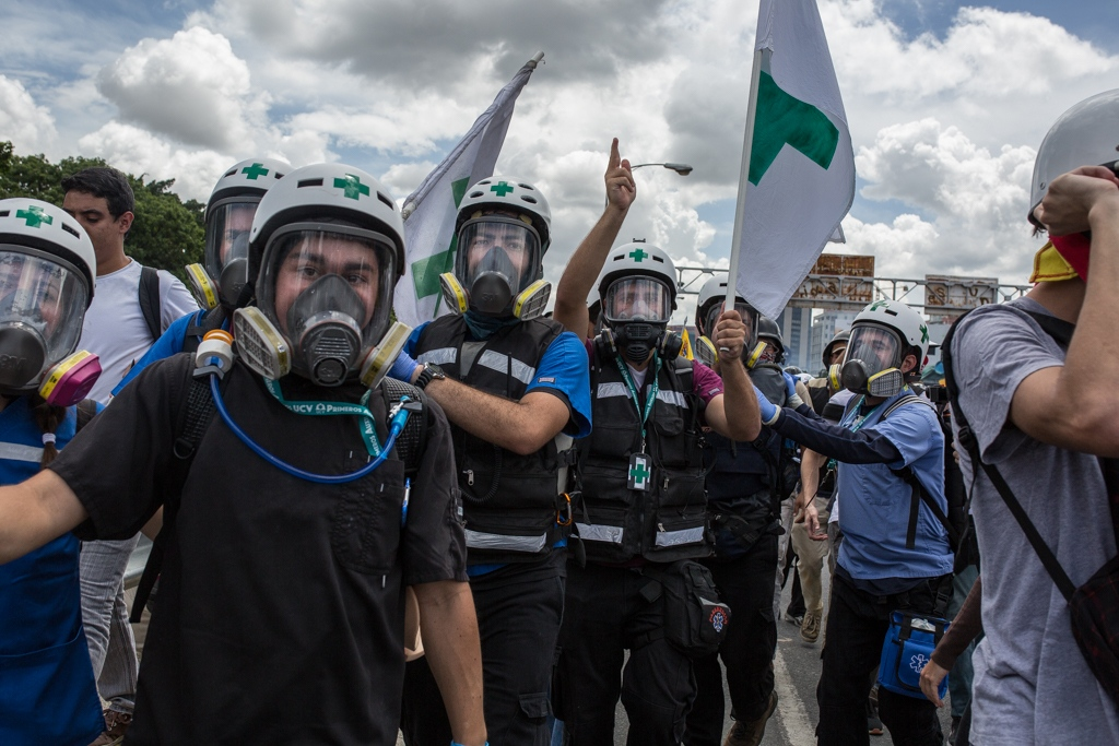 A group of green cross volunteers withdraw to the protest area when attacked with tear gas by the military forces. Francisco Fajardo highway, Caracas, Venezuela. June 19, 2017.