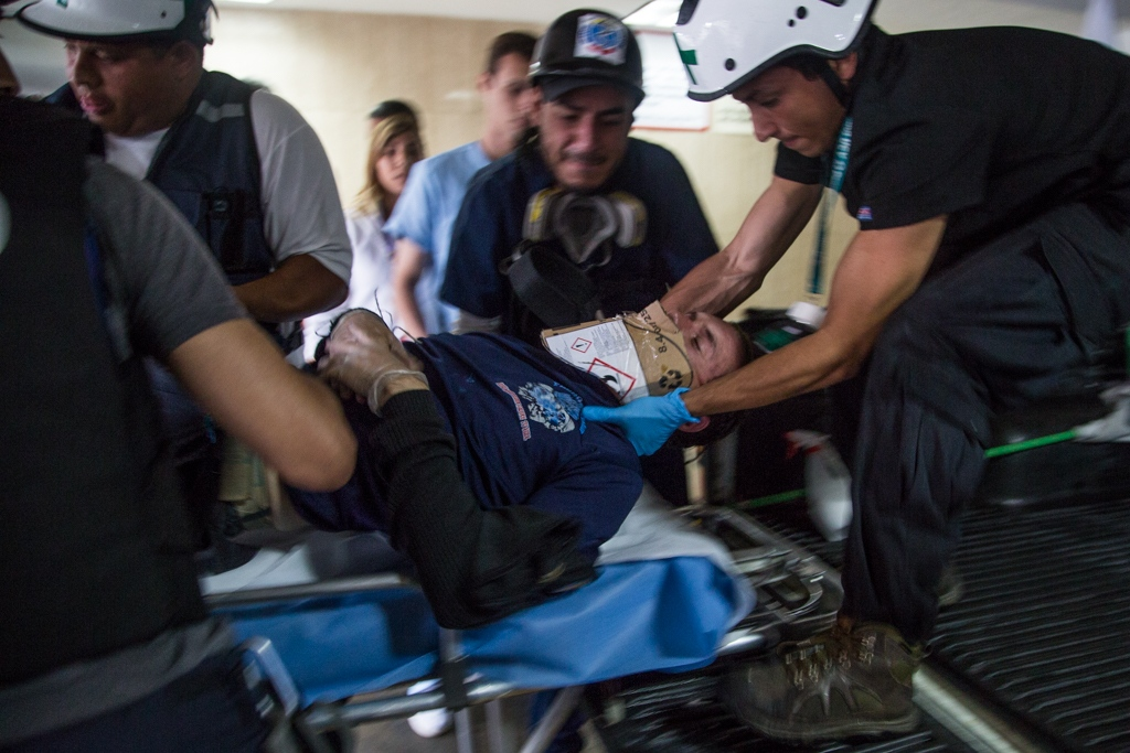 Volunteers members of green cross evacuate a severe injured person from the protest area to take him to a near health care center. Avila Clinic, Caracas, Venezuela. June 28, 2017.