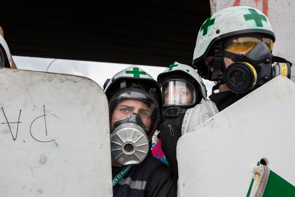 A group of green cross members protect themselves from the tear gas canisters thrown by the military forces using wooden shields. La Carlota, Caracas, Venezuela. June 24, 2017.
