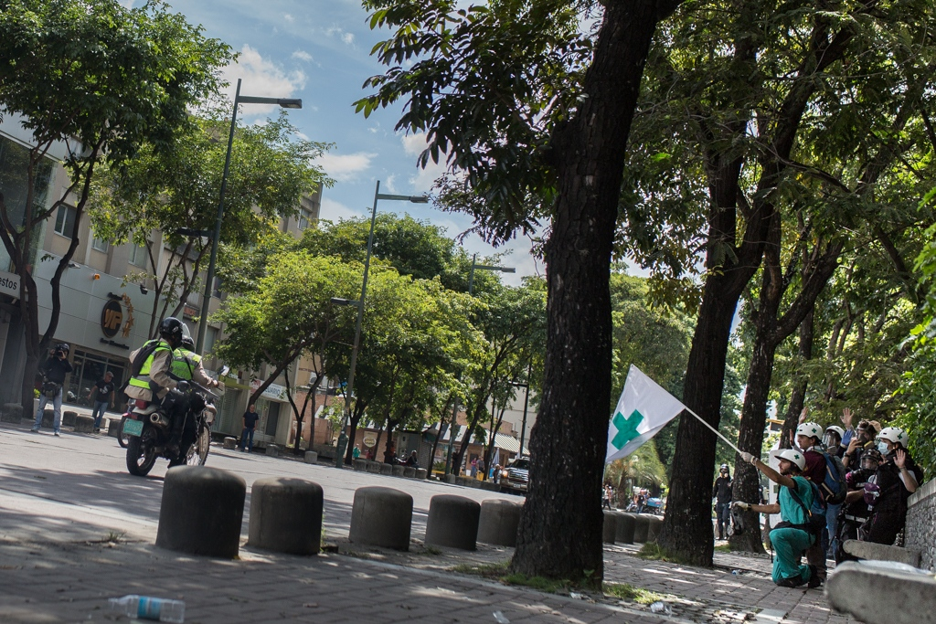 Volunteers members of green cross kneel and rise the institutional flag as a police motorcycle passes by in order to avoid a possible attack against them. In several opportunities members of green cross have been attacked by the police or the military forces. Las Mercedes, Caracas, Venezuela. June 19, 2017.