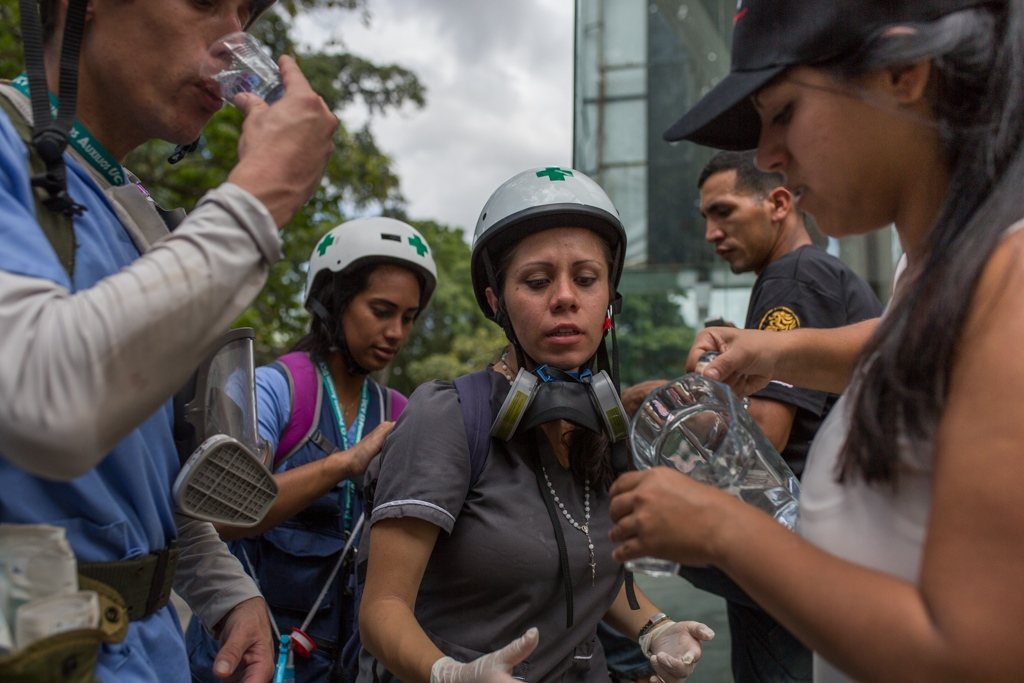 A girl offers some water to a group of volunteers green cross members in a brief moment of calm during a rally against Venezuelan government. Las Mercedes, Caracas. Venezuela. June 19, 2017.