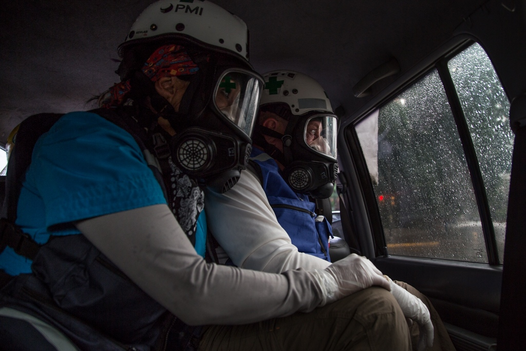 Two experienced Doctors, Members of Green Cross observes the protest from the inside of a vehicle used to transport injured people. Altamira, Caracas, Venezuela. June 28, 2017.