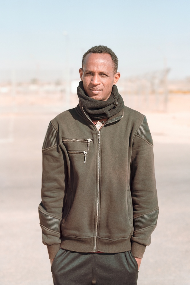 "Melake Tighanse, 26 – Eritrea Melake has been in Israel since 2010. He has worked in Ashdod for six years, until he was taken straight from work to detention in Holot. In Eritrea, he had been studying chemistry but feared to fail his exams and thus be forcedly conscripted for military service. It took him a week on foot into Sudan; then another three weeks hitchhiking to get into Sinai in Egypt. The Bedouins who captured him threatened to sell his kidneys, should he not manage to come up with the ransom of 4,800 US dollars. His family sold everything they owned. ""If you don't have the money, they will do surgery right there and you die. Unless you have seen it with your own eyes, it is inconceivable."""