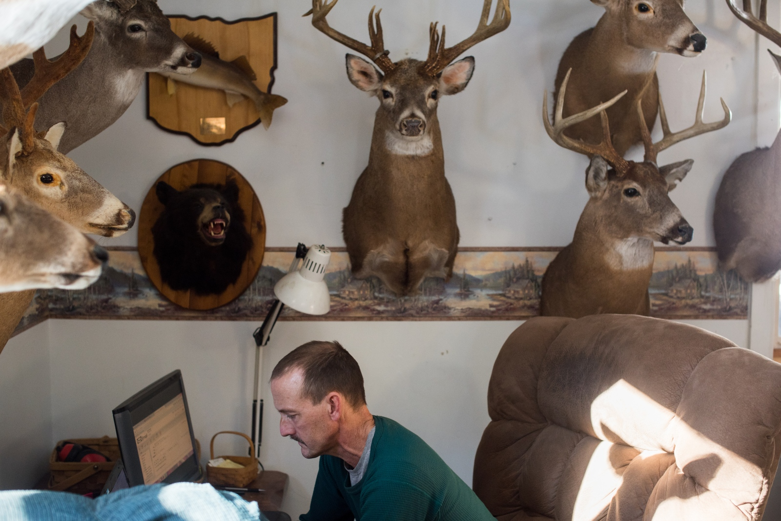Dave Rupe types on his computer beneath his collection of deer mounts at his home two miles outside the center of the village of Coolville, Ohio, in February 2015. Rupe, who has lived in the area his whole life, is a skilled craftsman and makes a living by both selling his wares and by finding and reselling online items ranging from old farm equipment to unwanted animals mounts—though those on his wall are not for sale.