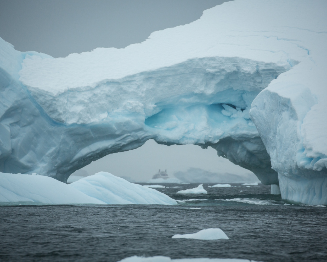 A distant cruise ship looms through an iceberg at the Yalour Islands, Antarctica. Under a highly regulated scheduling system, Antarctic cruise vessels generally go to great lengths to stay out of sight of one another.   While the wilderness experience may appear pristine to passengers, during the high season there can be over 20 ships operating simultaneously around the Antarctic peninsula.