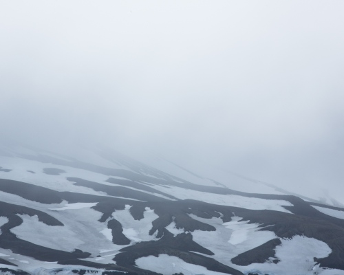 Low-lying fog enshrouds the mountains of Deception Island, a volcanic caldera in the South Shetland Islands.