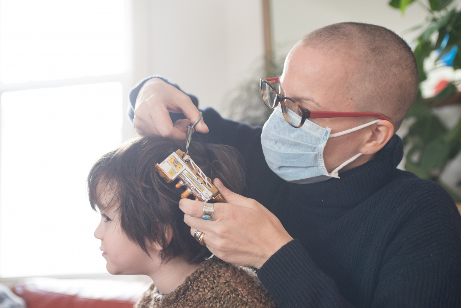 Anna cuts a toy train out of our son Jesse's hair. She must wear a surgical mask to protect her weakened immune system from catching ill from Jesse who is frequently surrounded by sick children at his daycare.