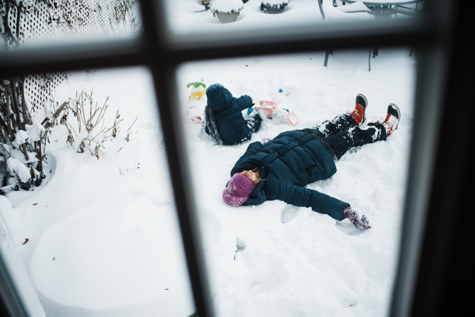 Anna makes snow angels outside in the family garden while our son Jesse plays with his toy trucks.