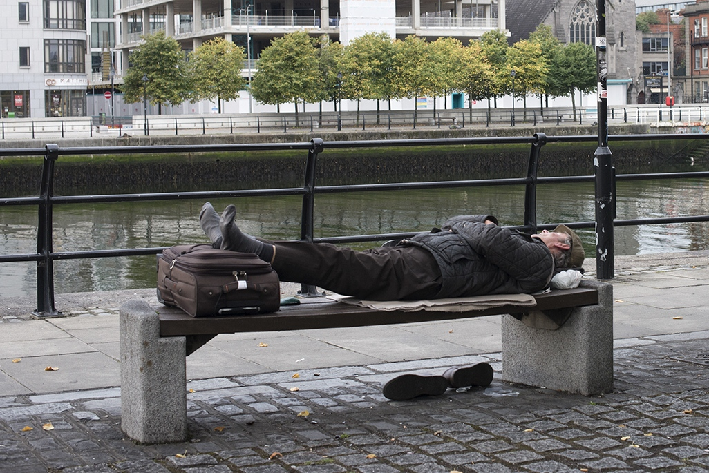 A man is sleeping near the Liffey River, Dublin