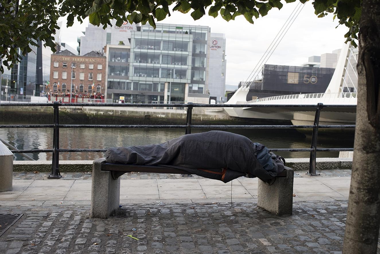 A man sleeping on a bench near the Liffey River.