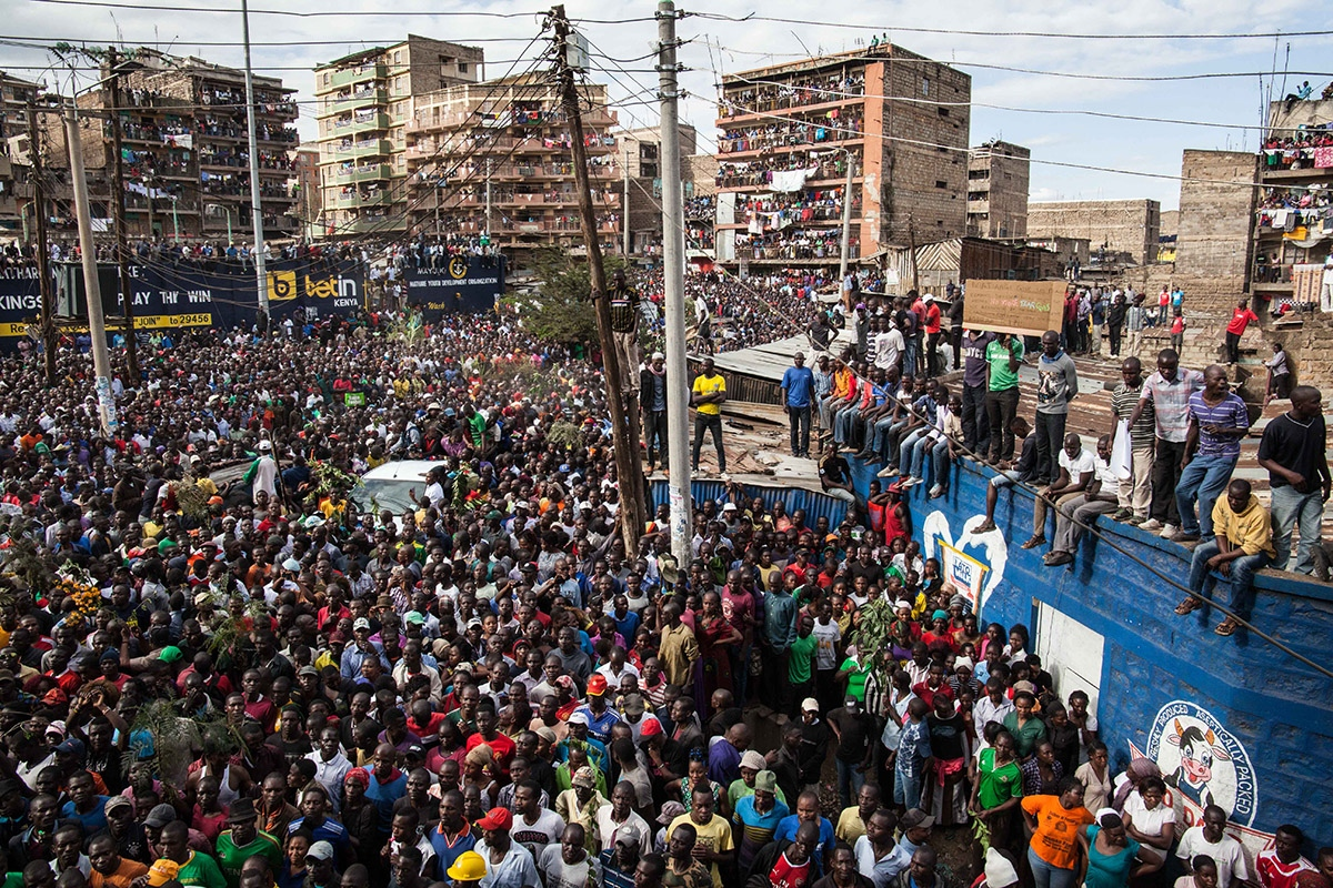 Thousands of supporters, some standing on rooftops, cheer the arrival of main opposition leader Raila Odinga in the Mathare area of Nairobi, Kenya Sunday, Aug. 13, 2017. Kenya's defeated opposition leader Raila Odinga on August 13 urged his supporters to boycott work, promising to announce on August 15 his strategy after an election he claims was stolen from him.
