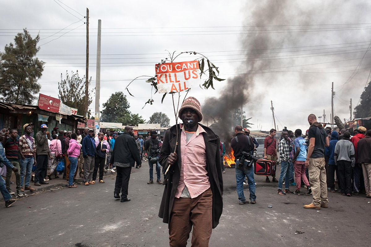 "Post-election protests continue in Nairobi slums for the third consecutive day. A man walks the streets of the slum of Kibera, the largest slum in Africa, with a banner reading one of the chants that have been heard for several days among the followers of presidential candidate Raila Odinga: ""They can't kill Us all""."