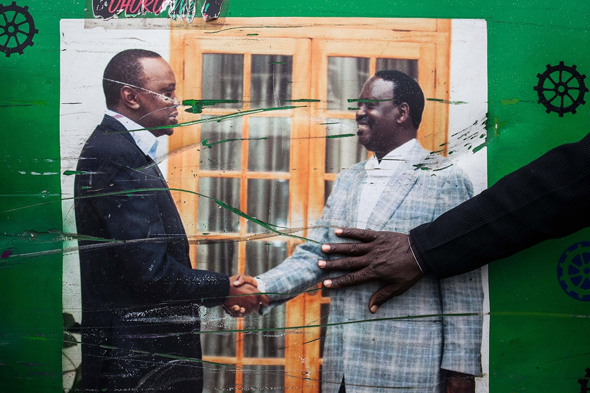 Driver of the traditional Matatus of Nairobi, buses set with different decorative motifs, carries in one of its sides a photo of presidential candidates Uhuru Kenyatta and Raila Odinga shaking hands after the 2013 elections, in which Kenyatta won the majority and Odinga accepted the results. The driver, Odinga's follower, rests his hand on his image.