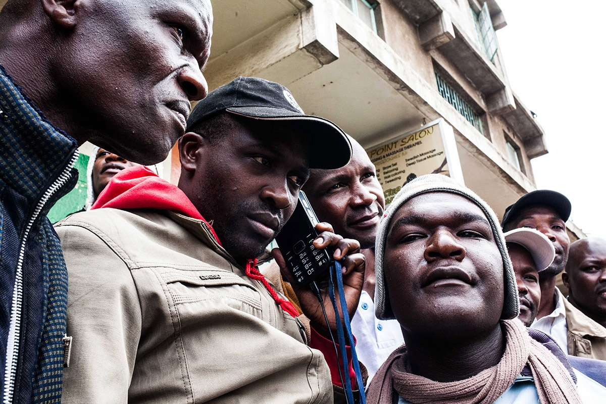 Several men, residents of the Mathare slum in Nairobi, one of the strongholds of opposition leader Raila Odinga, listen on a radio the official announcement of the election results on August 9, 2017, the day after the presidential election headlined by a too-close-to-call battle between incumbent Uhuru Kenyatta and his rival Raila Odinga.