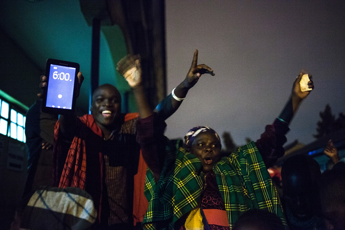 Inhabitants of Kibera, the largest slum of Africa located in Nairobi, celebrate the opening of ballot boxes at 6am after spending the night standing in line to vote in the presidential elections of August 8, 2017. Kenyans vote in general elections headlined by a too-close-to-call battle between incumbent Uhuru Kenyatta and his rival Raila Odinga.