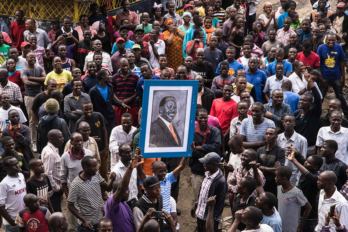 Supporters reach out to touch a painting of Kenyan opposition leader Raila Odinga, before he arrived to address thousands of supporters gathered in the Mathare area of Nairobi, Kenya Sunday, Aug. 13, 2017. Kenya's defeated opposition leader Raila Odinga on August 13 urged his supporters to boycott work, promising to announce on August 15 his strategy after an election he claims was stolen from him.