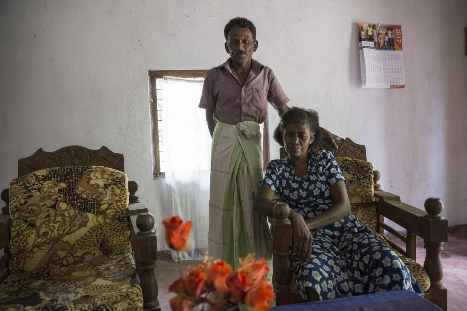 Maria Jasintha, 45, sits in her living room with her Sinhalese husband in Siriambadiya. He's a fisherman from the city of Negembo. Their son who works in Qatar as a construction worker is now classed as Sinhalese and as a result she is the last true Afro-Sri Lankan left in this household. Siriambadiya, Sri Lanka - January 2017