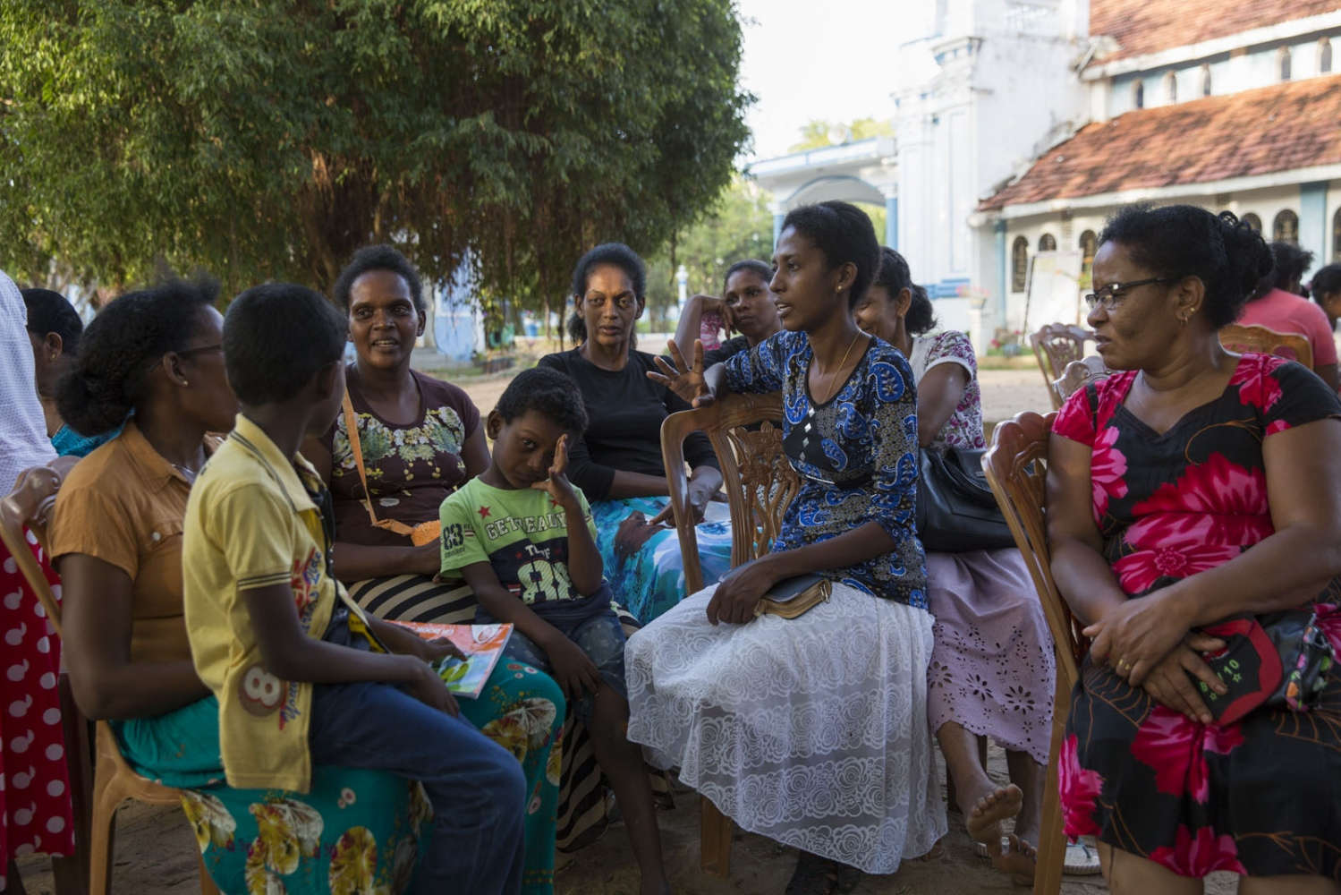 Litty Chrishanty, 38, (centre) chats with members of the community during a rehearsal for their 500 year celebration at St Mary's church. Puttalam, Sri Lanka - September 2017
