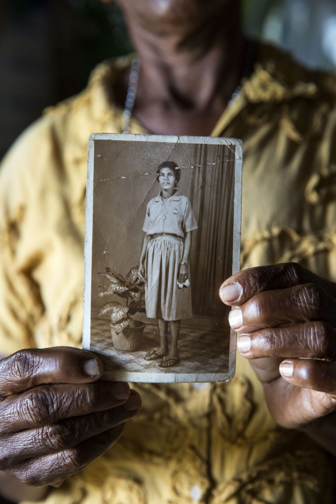 Daisy Perela, now 63, holds a photograph of her younger self close to the village of Kalypitiya. Kalpitiya, Sri Lanka - January 2017