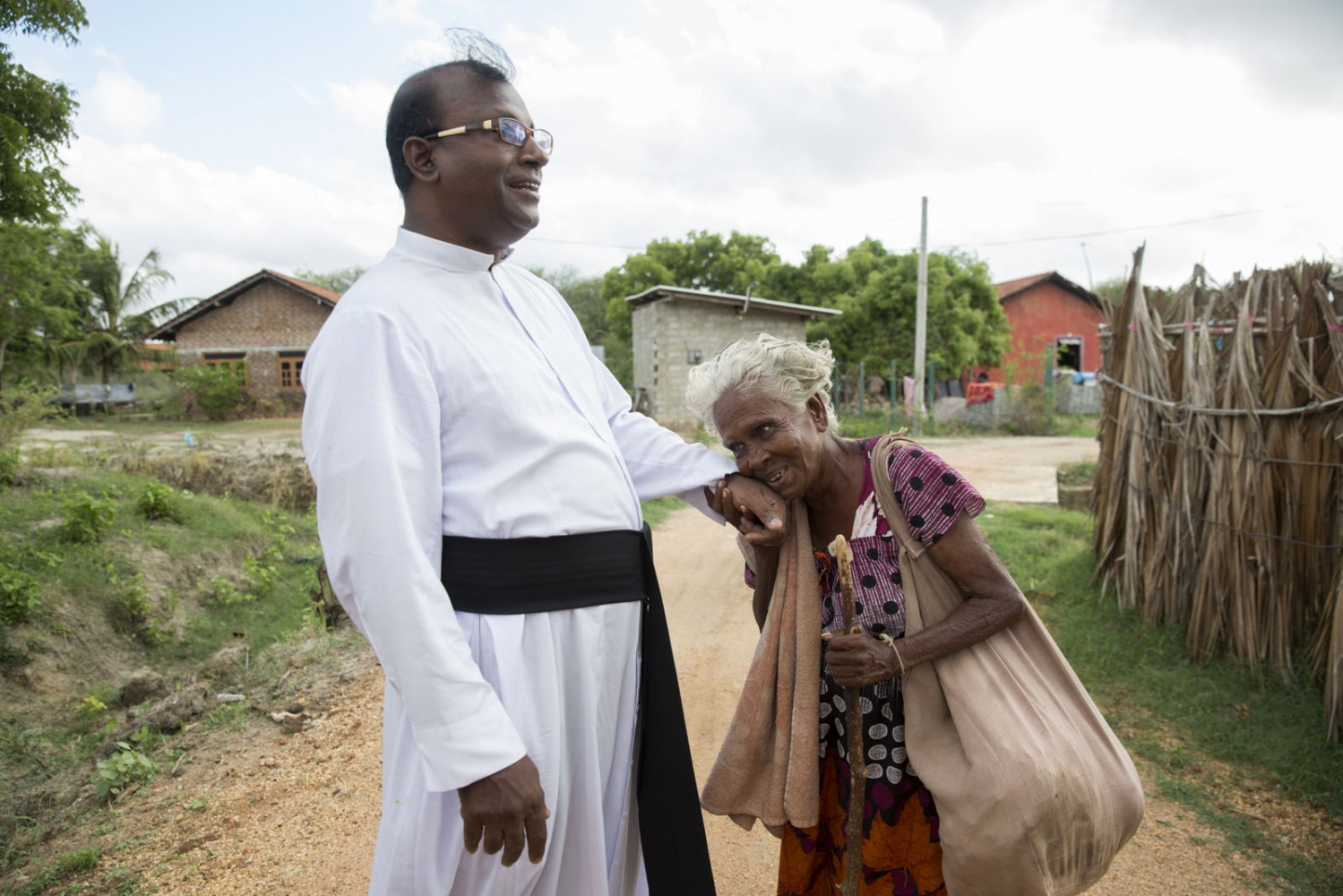 Father Kennedy of St Mary's Church is greated by Mary Margret, 88. The daughter of an Afro-Sri Lankan man she is almost totally blind and can't make it to Sunday Mass. Puttalam, Sri Lanka - September 2017