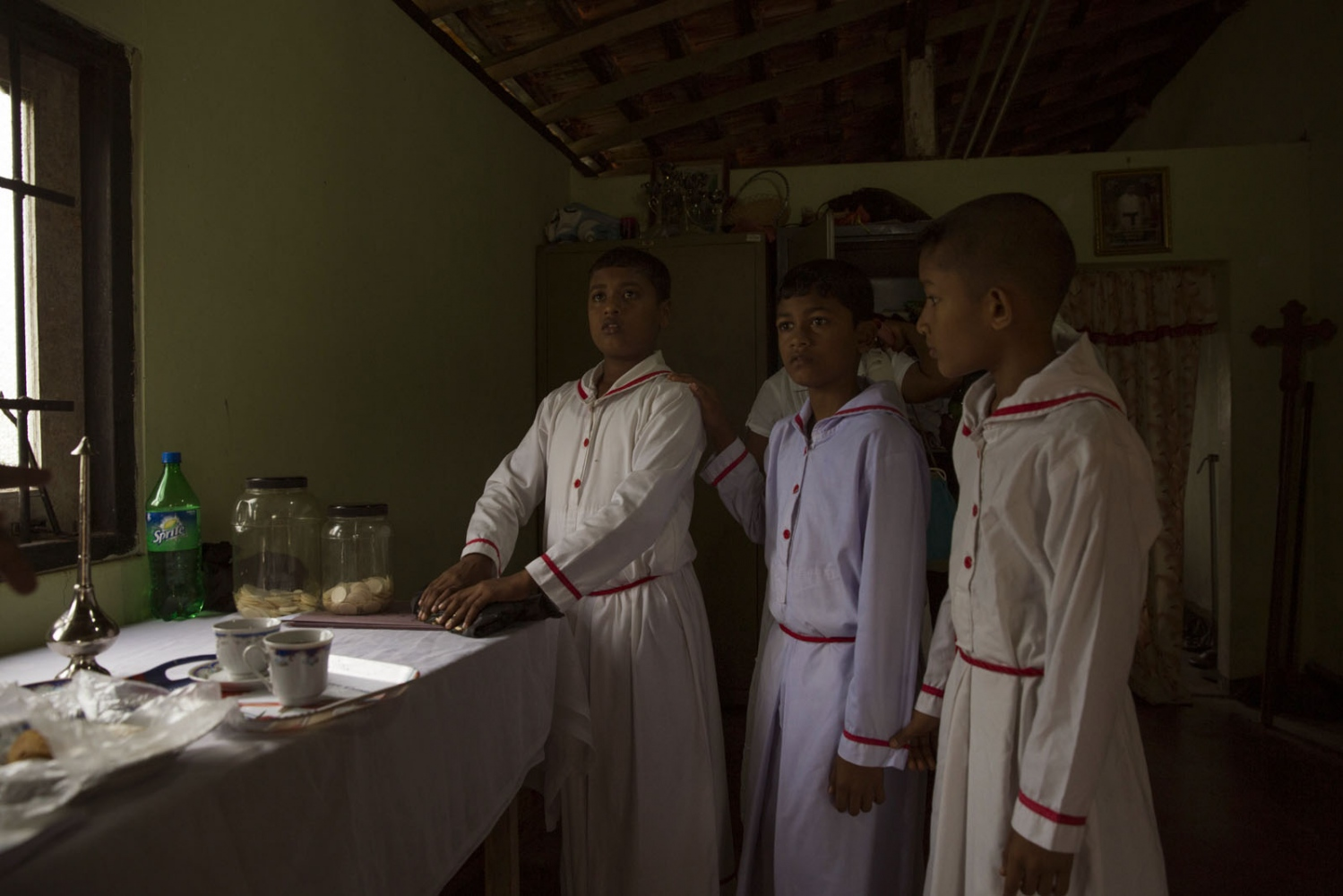 Jeewana Shehan, 13, (left) helping as an alter boy at the Roman Catholic church in Siriambadiya village. His mother is Afro-Sri Lankan but his father is Sinhalese and has lost his African appearance. Siriambadiya, Sri Lanka - January 2017