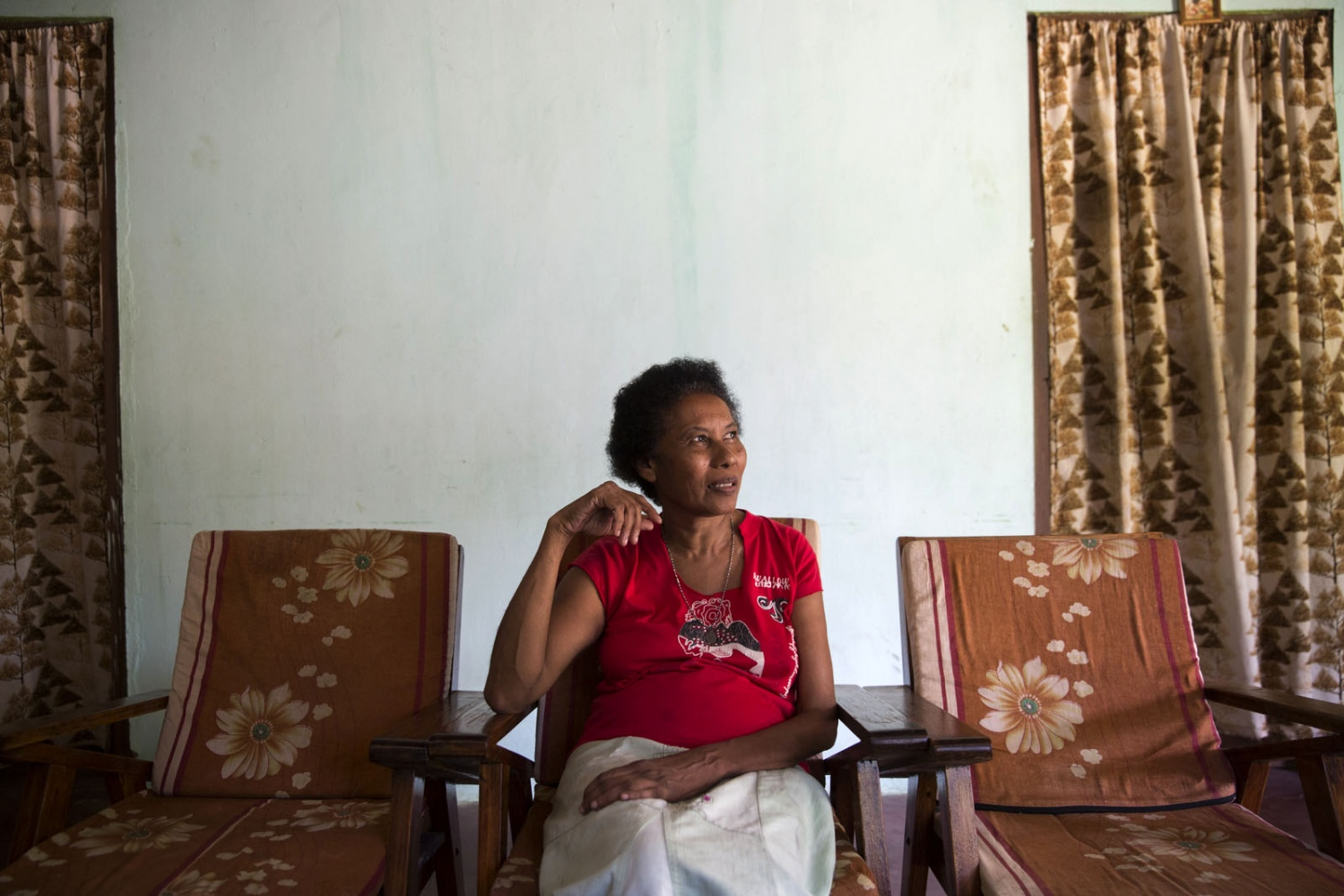 Rita Fernando, 65, daughter of an Afro-Sri Lankan mother and a Sinhalese father sits in her home in Siriambadiya village. Siriambadiya, Sri Lanka - September 2017