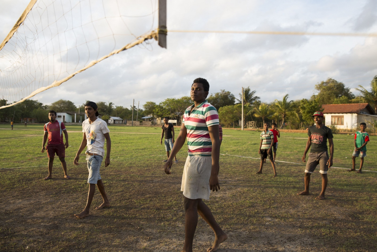 "Kovilage Anurudha Madumadawa, 18, plays volleyball with his friends in the Good Shed area of Puttalam town. At 6'4"" he towers above his friends. Puttalam, Sri Lanka - September 2017"