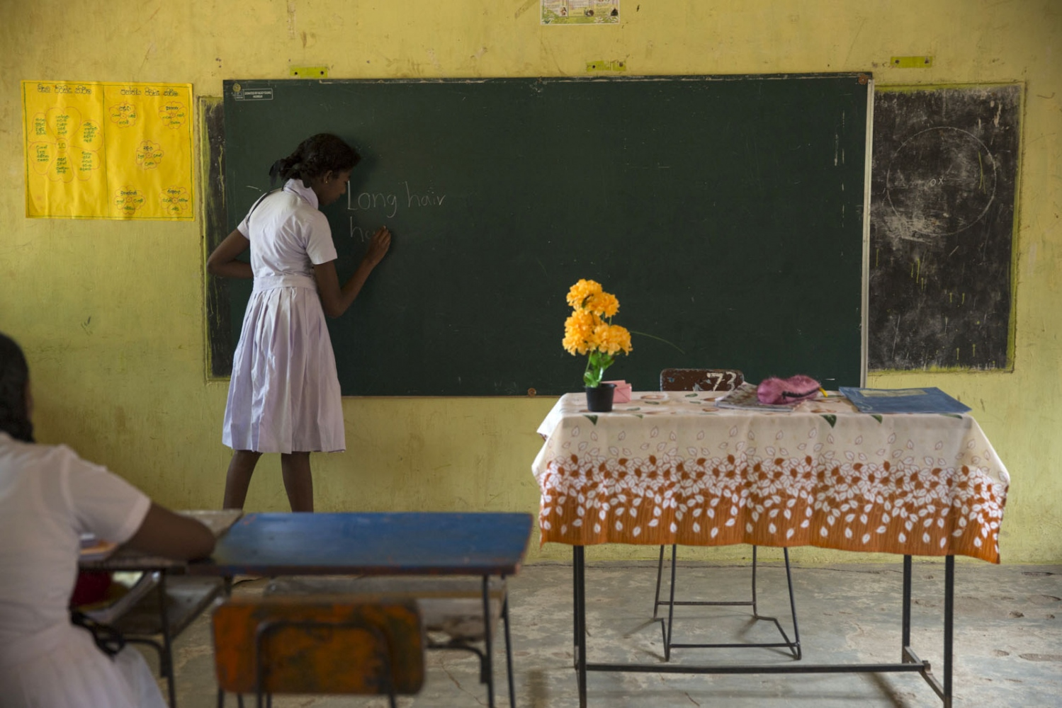 Afro-Sri Lankan Olivia Alexander, 14, practices writing english on the black-board at Siriambadiya school. Siriambadiya, Sri Lanka - January 2017