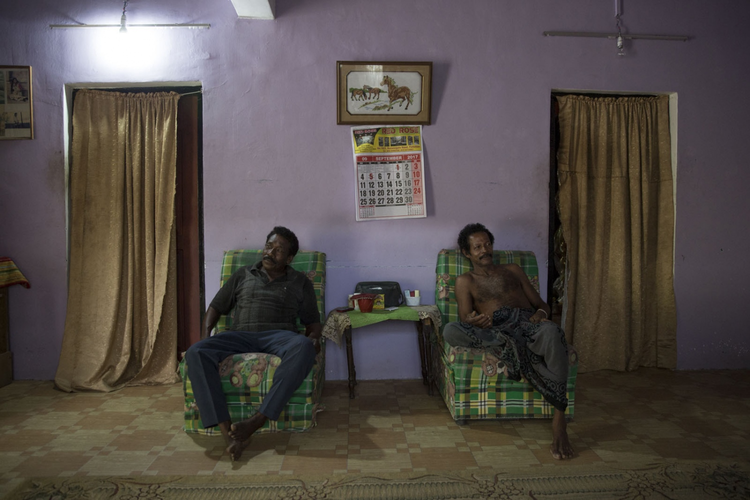 Solomon Linton (left) and Johnson (right) relax at Johnson's house in the Good Shed area of Puttalam town. Puttalam, Sri Lanka - September 2017