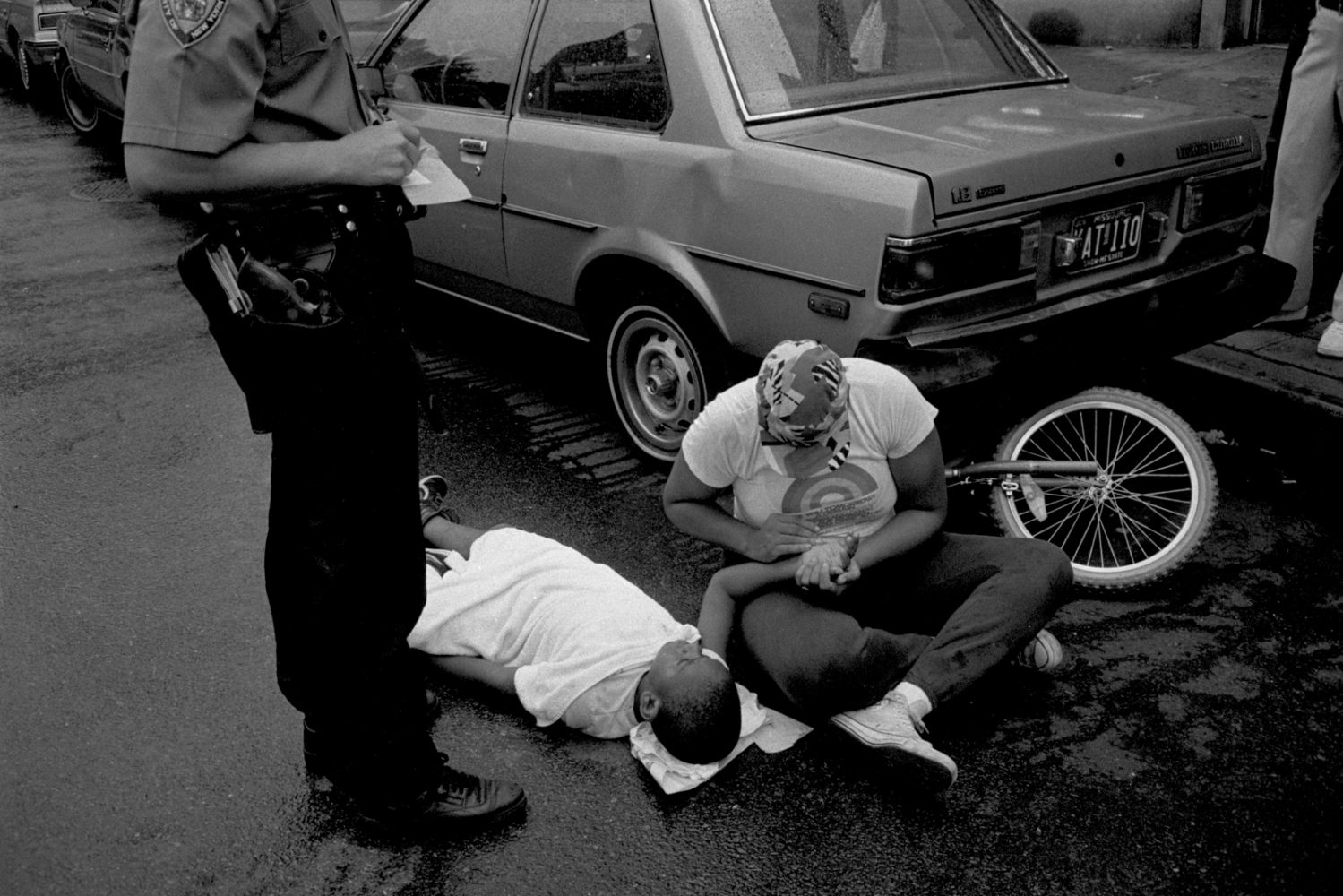 Boy riding his bike and hit by a car, is comforted by a stranger. Midtown 1987