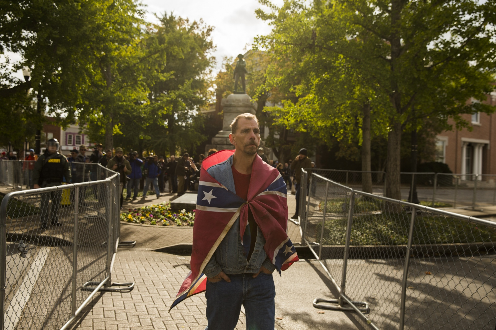 """Photography image - 10282017 - Murfreesboro, Tennessee, USA: A man wrapped in a confederate flag leaves Public Square as the confederate statue recedes behind him in downtown Murfreesboro, Tennessee. White Nationalist groups gathered for a """"White Lives Matter"""" rally in downtown Shelbyville, Tennessee earlier in the day, but canceled a second rally in Murfreesboro. The rally, and the counter rally in Shelbyville were the largest such gatherings since the deadly Charlottesville Unite the Right rally in August.  A coalition of neo-Nazis and white nationalists  including the Nationalist Socialist Movement, Traditional Workers Party, Vanguard America and Anti-Communist Action, and League of the South, were present.  The White Nationalist and neo-Nazi groups gathered at Henry Horton State Park 45 minute from Murfreesboro, but dispersed when members of the media arrived.   (Photo by Jeremy Hogan)"""