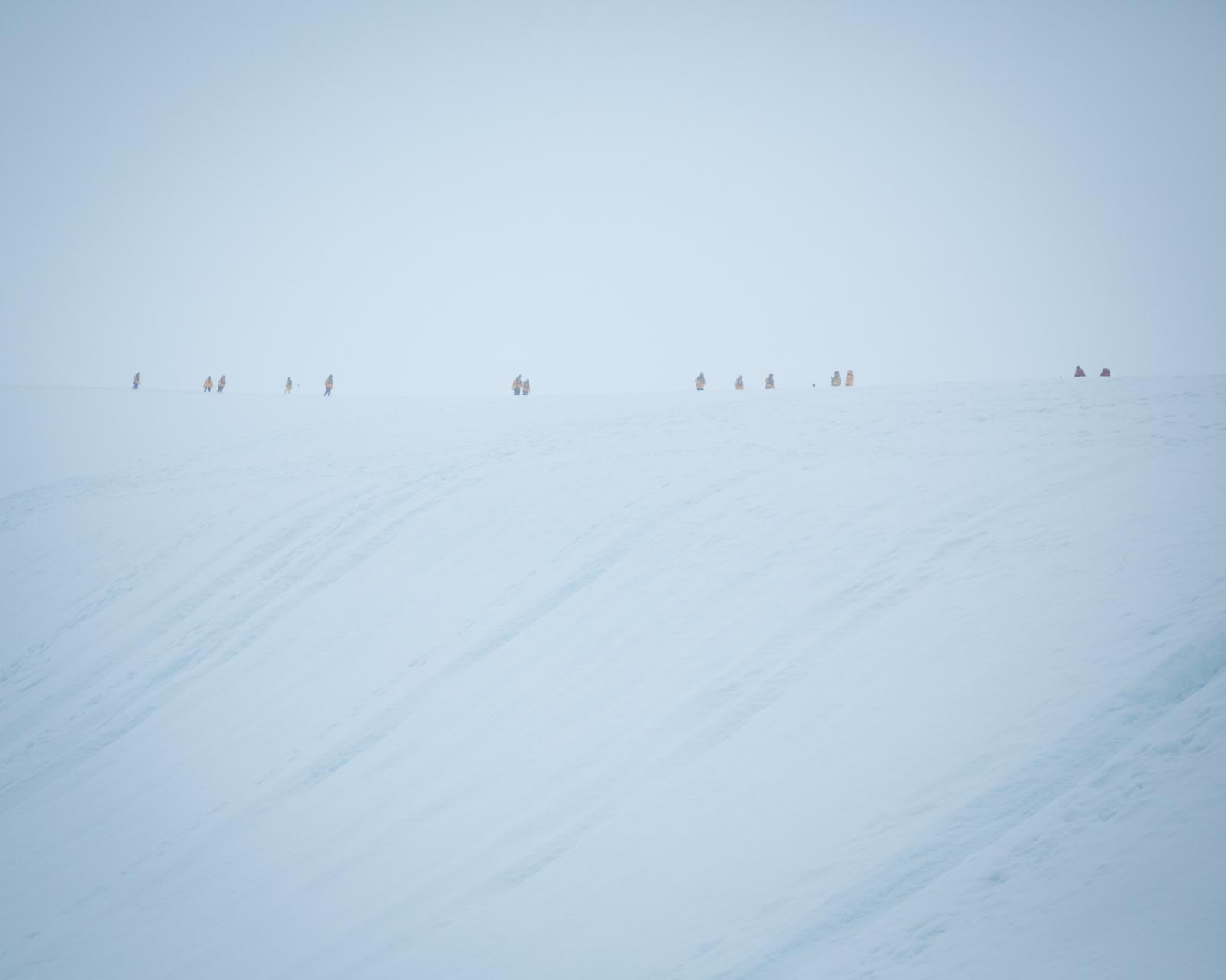 Tourists dot the horizon at Neko Harbour, Antarctica.