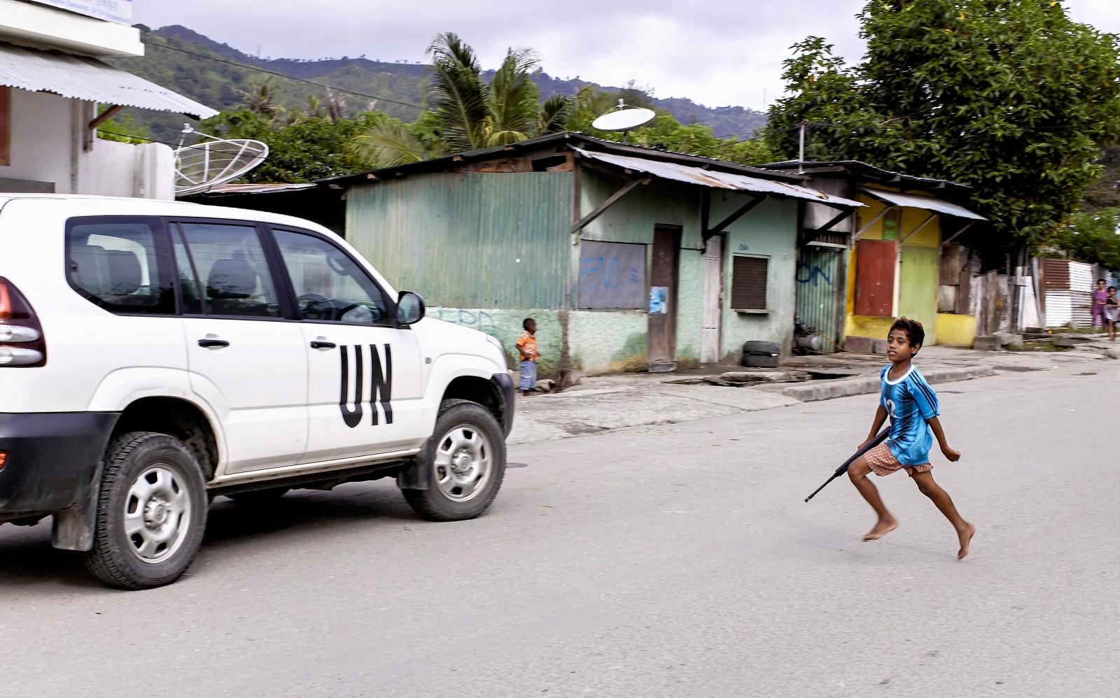 A boy carrying a gun running towards a UN...