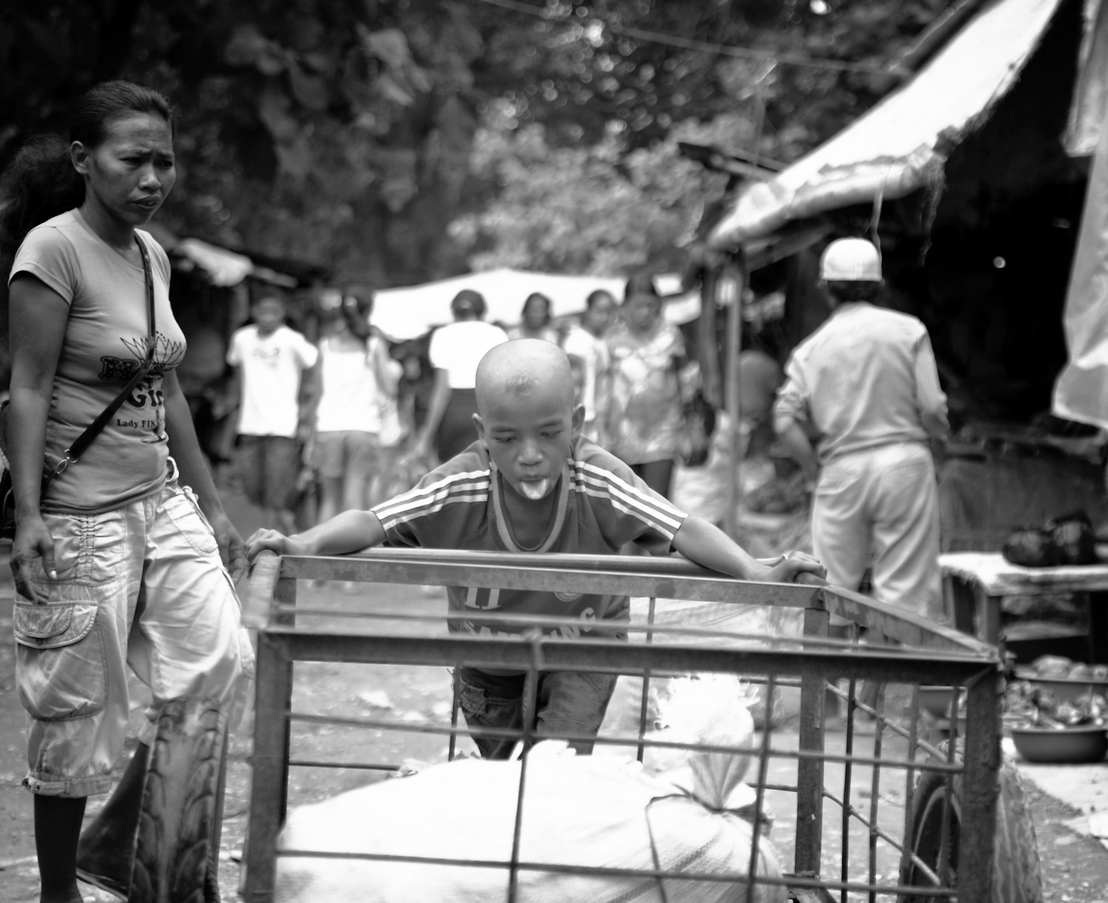 A young boy pushes a heavy metal cart at a East...
