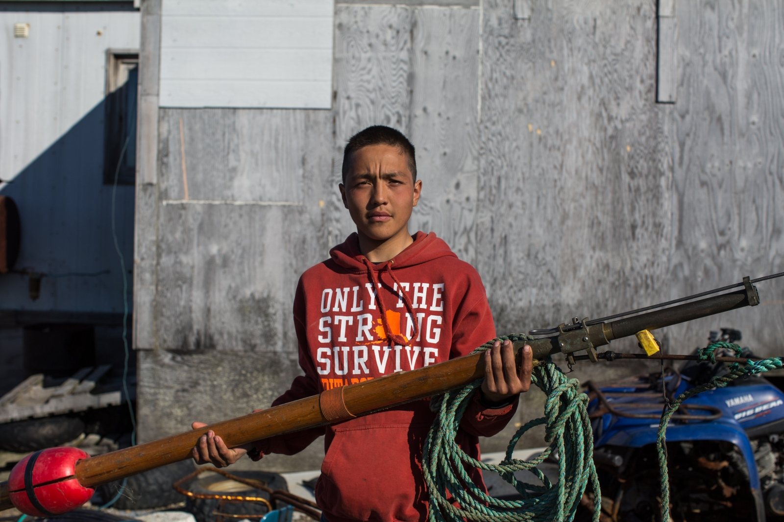 Chris Appassingok holds a darting gun outside of his family's home in Gambell, Alaska.