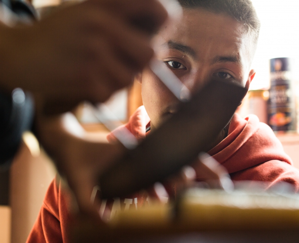 Chris Apassingok watches his sister, Danielle Apassingok, 17, as she cuts mungtuk with an ulaaq in the kitchen of their home.