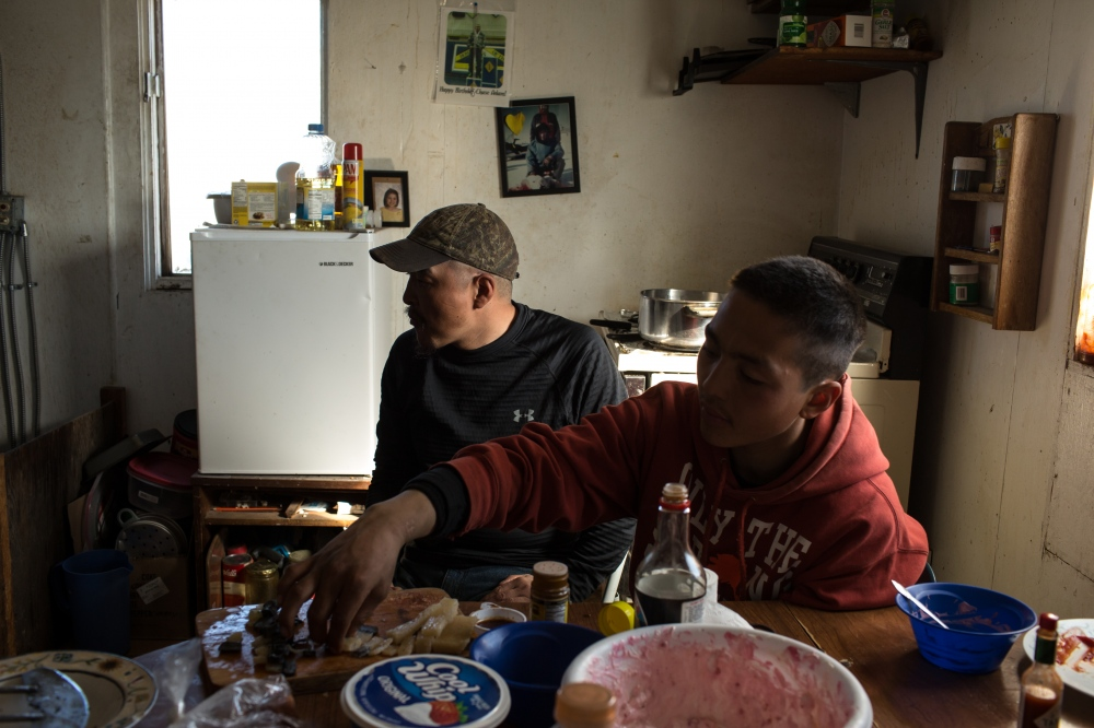 Danielle Apassingok, 17, cuts mungtuk with an ulaaq in the kitchen of her home. The mungtuk is from the bowhead whale her brother Chris struck in April.