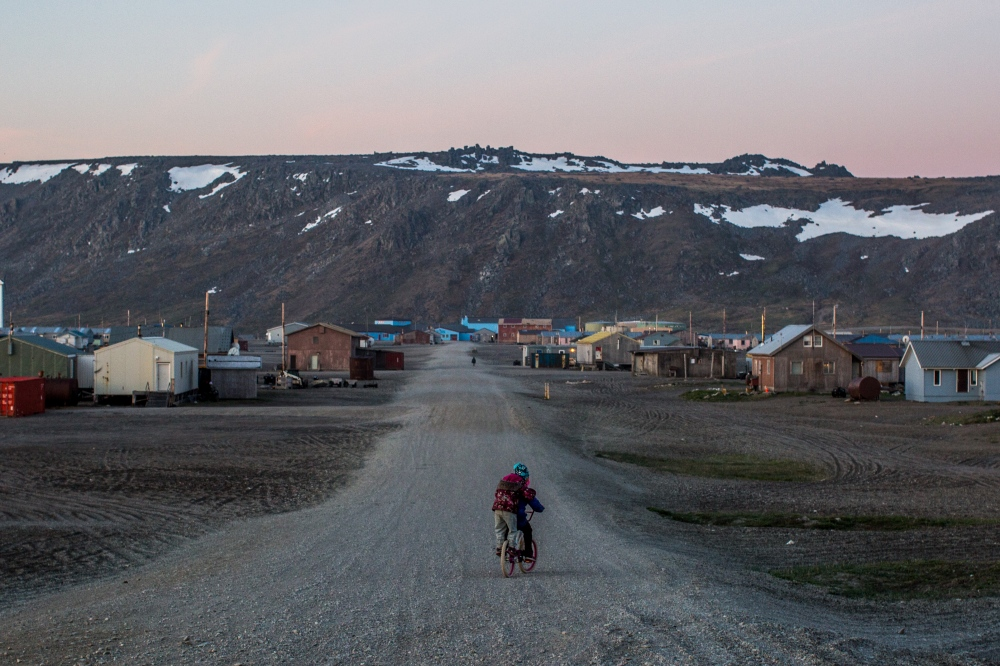Two girls ride a bicycle together at around 2:00AM in Gambell, Alaska. It's normal to see games being played and people out and about during the wee hours of the morning during the summer months, when the village does not experience true night; twilight falls around 2:00AM and lingers until sunrise at 5:00AM.