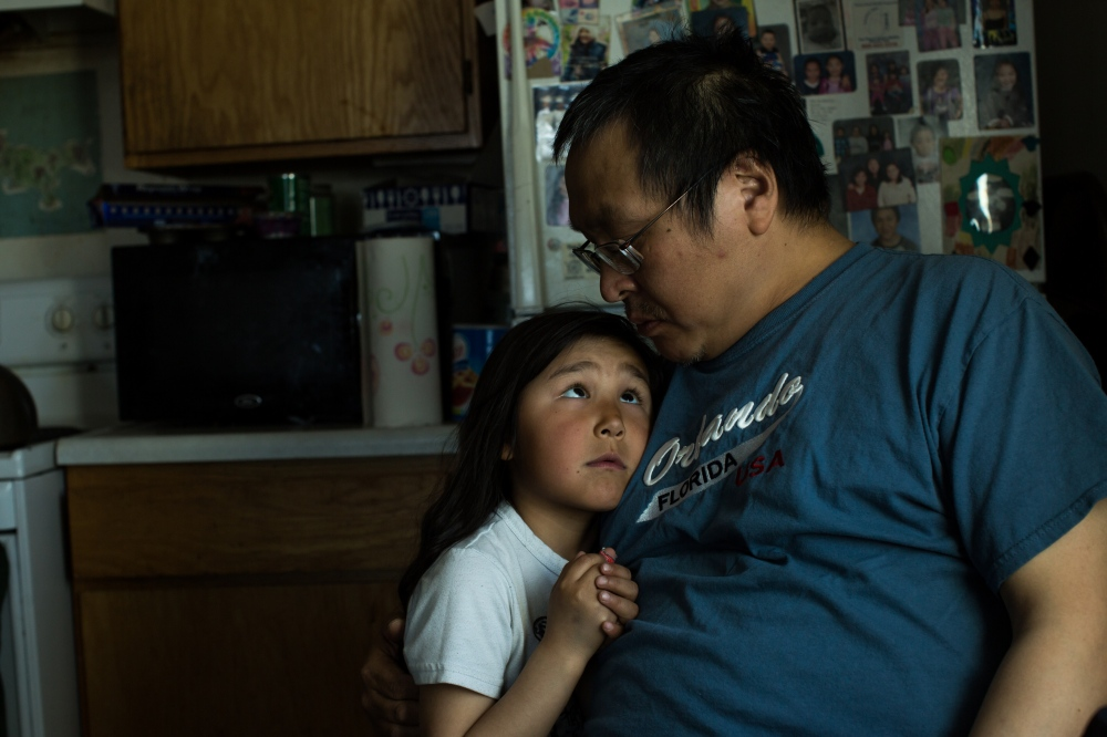 Merle Apassingok, Chris Apassingok's uncle and Daniel Apassingok's brother, talks with his 5-year-old granddaughter, Haylee, in his home in Gambell, Alaska.
